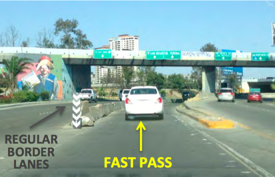9. The border entrance will be straight ahead. For Fast Pass, you will follow signs for Col. Federal in the third lane from the left, going just to the RIGHT of the concrete barrier (where the white car is headed in the photo). You will continue up the ramp and over a bridge.